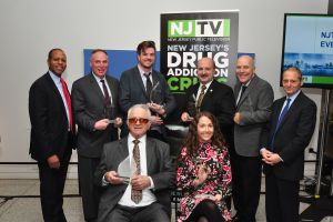 NJTV's Healthy NJ: new Jersey's Drug Addiction Crisis Everyday Heroes event on January 18, 2017 at the Trenton State Museum. Standing L-R NJTV News Correspondent and Master of Ceremonies Michael Hill; NJ Advance Media writer Stephen Stirling; Executive Director of Partnership for a Drug-Free New Jersey Angelo M. Valente; Ocean County Prosecutor Joseph D. Coronato; Endeavor House Medical Director Dr. Christopher Johnston; and NJTV General Manager John Servidio Seated: President and CEO of The Overdose Prevention Agency, Paul Ressler and writer Alicia Cook. Award recipient Patty DiRenzo is not pictured. Photo I. George Bilyk/NJTV
